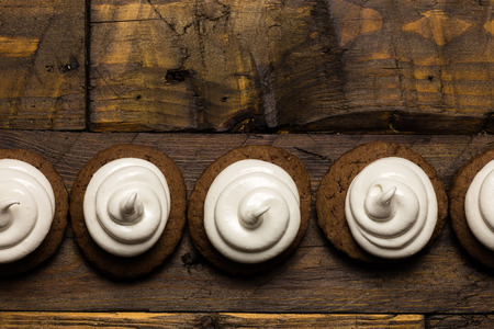 Hot chocolate cookies with marshmallow meringue on dark brown rustic wood background
