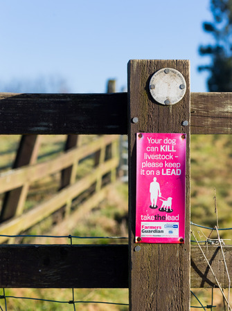 Finmere, Oxfordshire, United Kingdom, January 05, 2017: Public footpath marking on fence with purple warning 'Your dog can KILL livestock - please keep it on a LEAD' part of the initiative for Farmer calls for change to dog microchipping law.