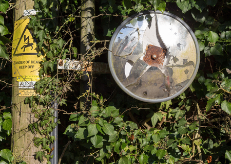 Finmere, Oxfordshire, United Kingdom, January 05, 2017: Broken traffic safety convex driveway mirror attached to wooden electricity pylon on Fulwell Road, Finmere, Buckingham.