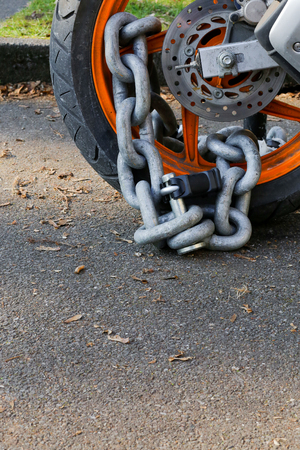 alarming: Motorcycle anti-theft chain with padlock security lock on rear wheel, protection against theft Stock Photo