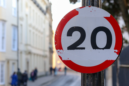 20 miles per hour mph speed limit damaged road sign on Oxford street