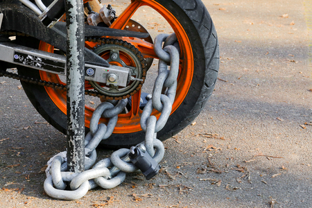 Motorcycle anti-theft chain with padlock security lock on rear wheel, protection against theft Фото со стока