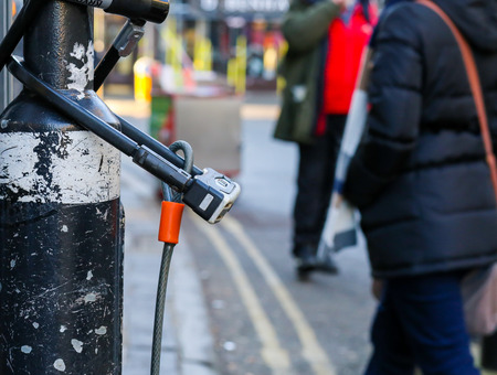 Broad Street, Oxford, United Kingdom, January 22, 2017: U-lock secure bicycle locks on light post on Broad street, Oxford city centre, England