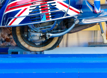 Broad Street, Oxford, United Kingdom, January 22, 2017: Union Jack flag painted Piapgio Vespa Motor Scooter with empty old vintage tire in Cool Britannia gift shop store, selling souvenirs and other british english gifts on Broad street, Oxford city centr