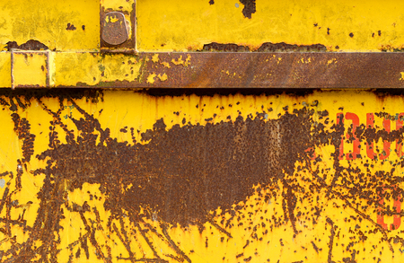 pealing: Old rusting metal skip container with yellow pealing scratched paint and orange red letters Stock Photo