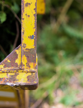 pealing: Old rusting metal skip container with yellow pealing scratched paint and green background Stock Photo