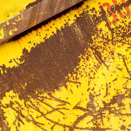 saltar: Contenedor de saltos de metal oxidado viejo con pintura rasguñada pealing amarilla y letras rojas naranjas