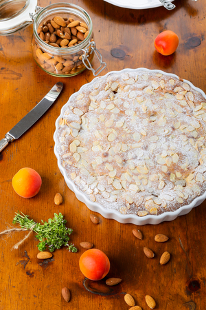 Crustless apricot frangipane tart with almonds and aromatic lemon thyme on rustic brown pine table
