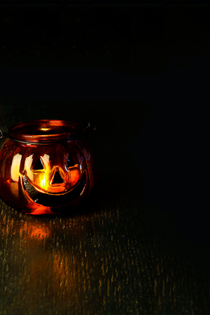 Halloween pumpkin head bowl lantern on dark background with copy space
