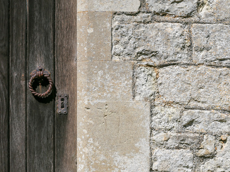 Old weathered wooden door with rusty iron lock and knocker on ancient white stone wall