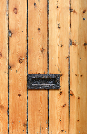 Old rustic cottage striped wooden door with metal letterbox Stock Photo