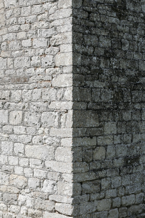 Old corner stone wall with vertical shadow line
