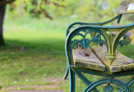 Old turquoise blue painted cast iron garden bench with weathered wooden planks, blurred green background