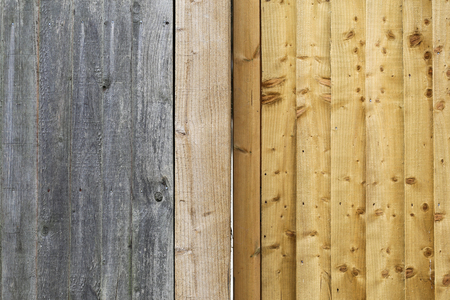 Old gray weathered fence planks and new light gold brown wood background Stock Photo