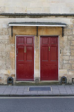Two dark red front doors on the stone wall, street pavement with boot scrapers Stock Photo