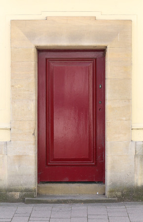 Abandoned dark red front door on the stone wall, street pavement Stock Photo
