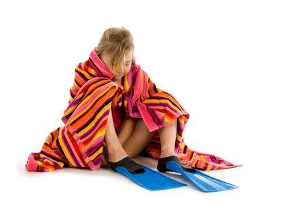 flippers: Chica envuelta en una toalla tratando de poner en aletas Foto de archivo