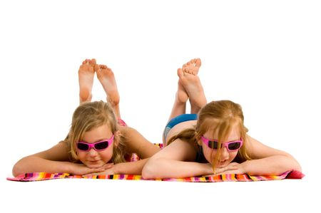 young girl feet: Two young girls lying in the sun on a towel Stock Photo