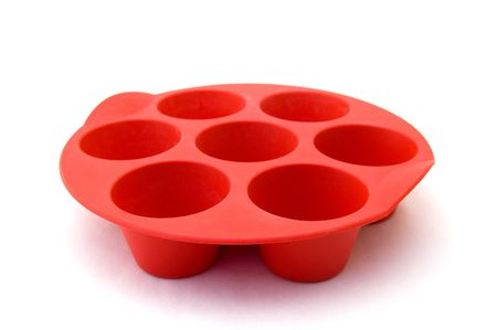 silicone: A red silicone muffin mold on a white background
