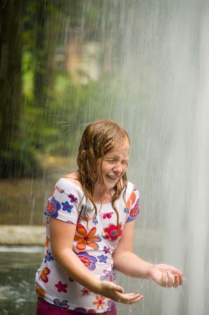 wet clothes: Ni�a de pie bajo una fuente mojarse