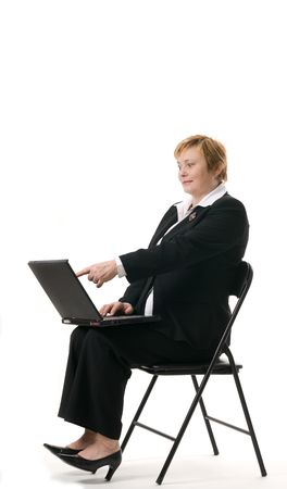 Mature businesswoman searching internet on her laptop computer