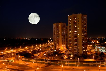 city view at night with moonlight, streetlights and highway