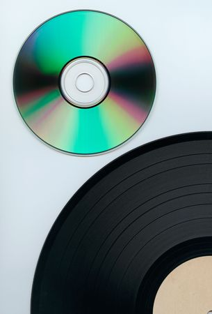 Close up of a cd and partial record over white background