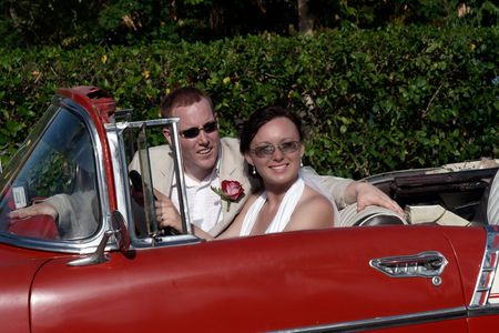Husband and wife portrait sitting in classic car photo