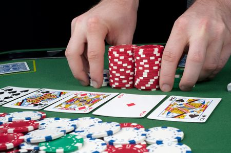 All in motion with five cards face up in front of a pot of chips Redactioneel