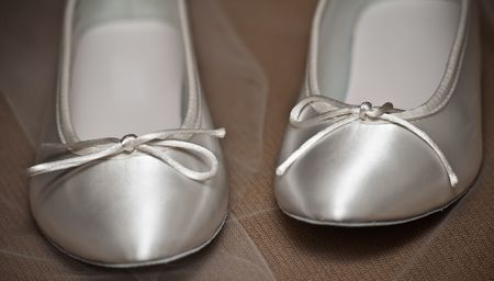 Close up of white shoes on wedding veil