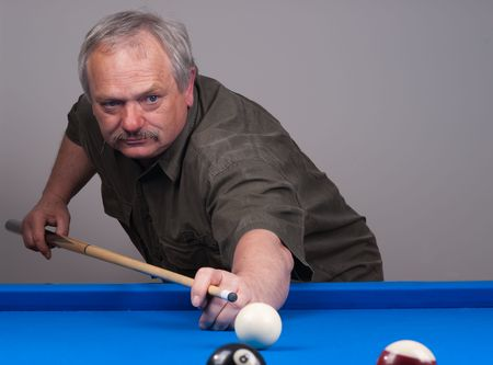 Man playing pool on blue felt billiard table and taking a shot with his cue.