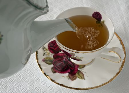 Pouring green tea into the cup on the plate and breakfast table