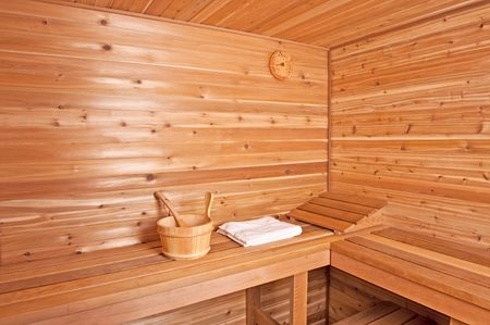 a wooden sauna with a bucket and towel inside the room
