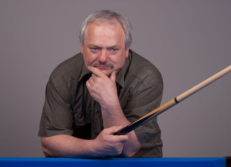 cue stick: man resting his arms on the pool table holding a cue stick