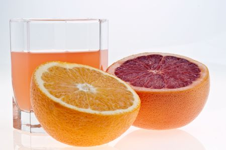 two and a half: two halves of grapefruit and juice in glass on white Stock Photo