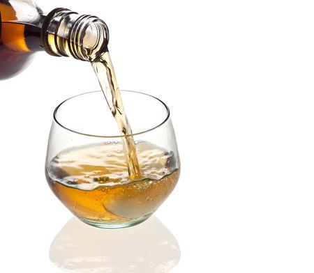 A glass of whiskey being poured on a white background