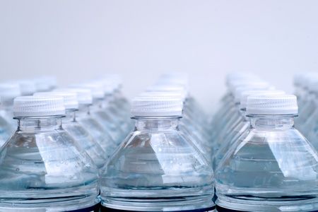 Rows of Bottles of water with bubbles on white background