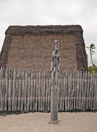 하와이의 빅 아일랜드에있는 고대 피난처 인 Puuhonua O Honaunau의 성소를 지키기위한 Hale o Keawe (하와이안 신의 목조 이미지)