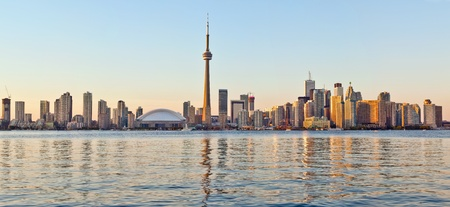 The landmark Toronto downtown view from the center island  Scenic view of the CN Tower illuminated by the iconic downtown skyline of skyscrapers and high rise condominiums reflecting in Lake Ontario