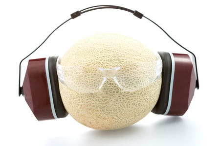Industrial protective headphones and safety glasseson on the melon, isolated on white background