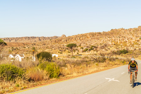 The Pakhuis Pass, South Africa - May 6, 2015: Cyclist riding the bike through The Pakhuis Pass . Th Pass lies roughly 20 kilometres outside of Clanwilliam with incredible views from the top of the pass onto the Karoo. Editorial