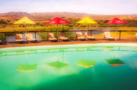 Noordoewer , South Africa - May 2, 2015: View at swimming pool and Orange river in Felix Unite Camp in Noordoewer, South Africa. 新聞圖片
