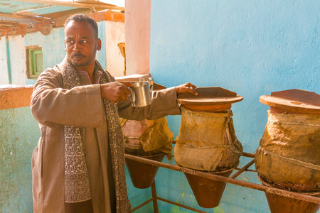 man drinking water: Easter desert, Egypt - January 11, 2015: Man drinking water from water container. Clay containers with drinking water and old can attach by a cord, which offer water to people passing by. They are popular in Egypt. Most are set in the shade to keep the wa