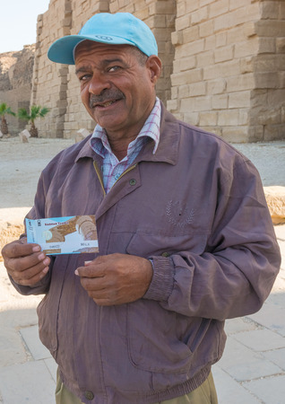 Luxor, Egypt - January 15, 2015: Man in Luxor showing entrance ticket to the temple. Editorial