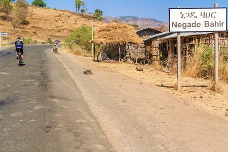 village man: Negade Bahir, Ethiopia - February 6, 2015: Man riding bicycle through Negade Bahir a small village in Ethiopia.