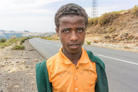 ali: Ali Doro, Ethiopia - February 16, 2015: Close up picture of the young boy staying by the road. Picture was taken when riding on the road number 3 near Ali Doro in Ethiopia.