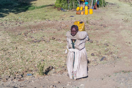 carrying the cross: Gondar, Ethiopia - February 10, 2015: Woman in Ethiopia carrying water tank on her back. Picture taken from the road near Gondar in Ethiopia. Editorial