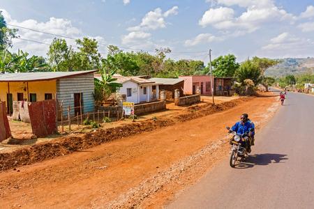 village man: Gwangwa, Ethiopia - February 23, 2015: Man is riding motorbike through small village of Gwangwa in Ethiopia.