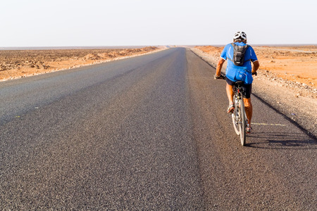 road cycling: Marsabit, Kenya - March 1, 2015: Man on bicycle cycling on Marsabit Moyale road in Kenya.