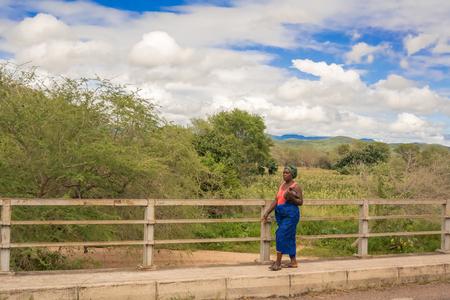 sabi: Sabi river, Malawi - March 23, 2015: Local woman is crossing bridge at Sabi river in Malawi